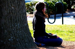 Girl meditating next to a tree