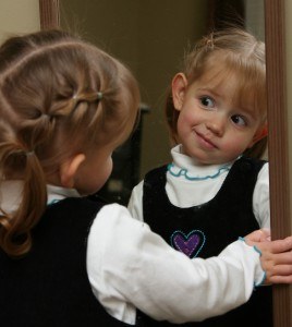 young girl saying her positive affirmations into the mirror